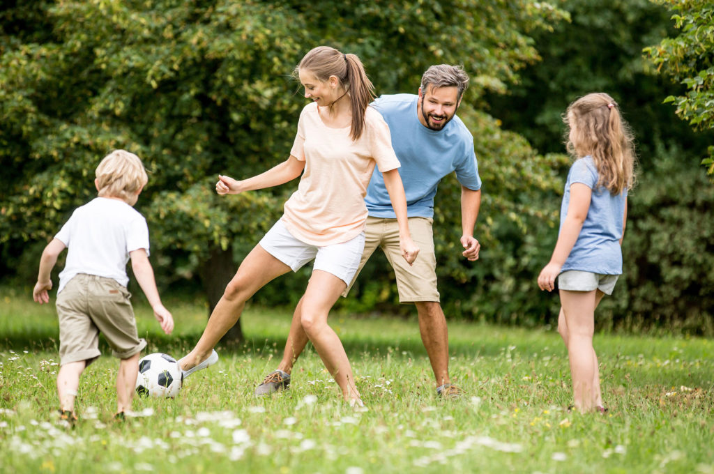 Family playing soccer in a park