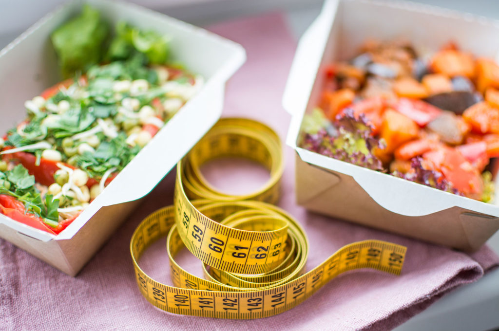 healthy meals next to a measuring tape.